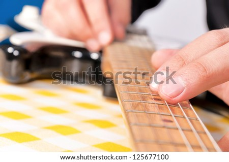 Closeup of man's hands playing bass guitar DOF focus on hand - stock photo
