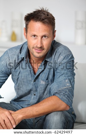 Closeup of man sitting in sofa - stock photo