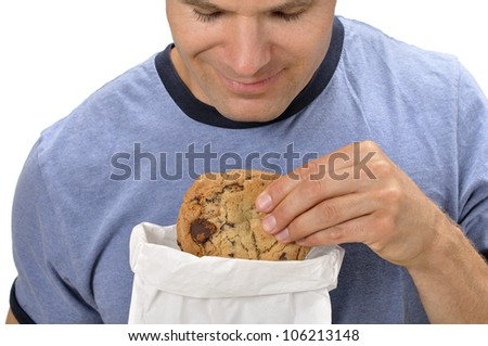 Closeup of man taking a big chocolate chip cookie out of a bag