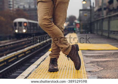 Closeup of  man wearing boots and jeans  in a subway station in New York - stock photo