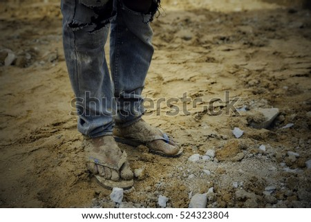 Closeup of man wearing sandals and blue jean standing on the ground,his legs dirty soil