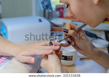 closeup of manicurist at work in the salon nail (shallow DOF; color toned image, focus on the finger)