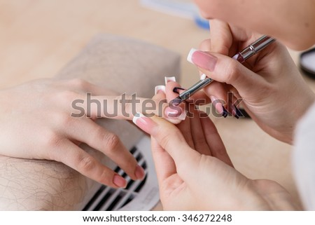 closeup of manicurist at work, painting nails in nail salon, manicure, focus on corrective stick - stock photo