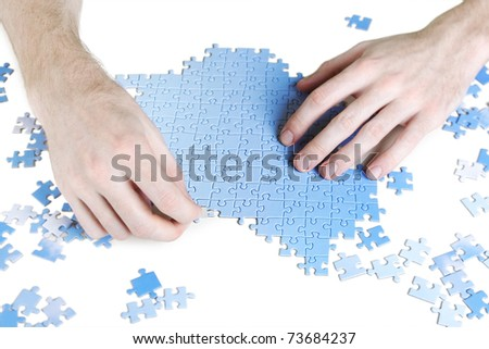 closeup of mans hands assembling blue puzzle pieces, isolated