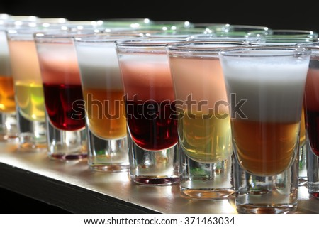 Closeup of many beautiful glasses with bright multicolored red yellow white and orange tasty alcoholic cocktail shots fresh liquid standing in line studio, horizontal picture - stock photo
