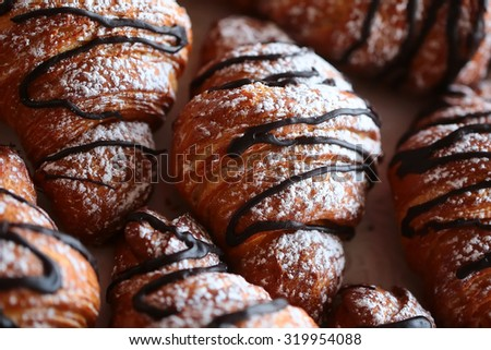 Closeup of many delicious fresh beautiful french croissants drizzled with black chocolate and sprinkled with white powdered icing sugar, horizontal pictre - stock photo