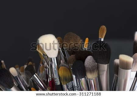 Closeup of many different professional natural make-up brushes for eyeshadow powder and facial foundation for visagistes black brown and white colors on grey background copyspace, horizontal picture - stock photo