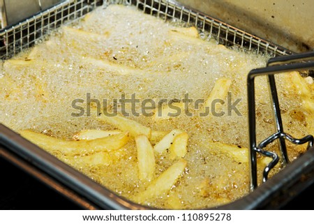 Closeup of many french fries in hot fat in a deep fryer - stock photo