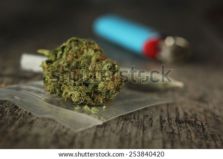 Closeup of marijuana joint and buds and blue lighter on a wooden table with a shallow depth of field - stock photo