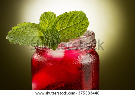 Closeup of mason jar of raspberry juice with mint leaves and lime wedges