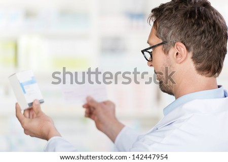 Closeup of mature male pharmacist reading prescription paper and medicine details in pharmacy - stock photo