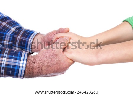 Closeup of mature man hands holding his daughter hands, care concept, over white background - stock photo