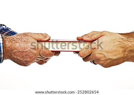 Closeup of mature mans hand giving a book to his son,conceptual image, over white background  - stock photo
