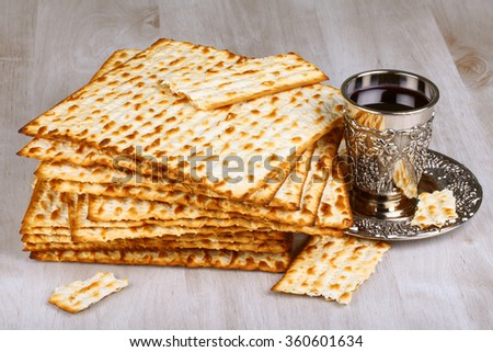 Closeup of Matzah with cup of wine on wooden table  - stock photo