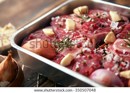 Closeup of meat in steel pan spices around: garlic, rosemary, onions; ready to cook in oven on wooden table