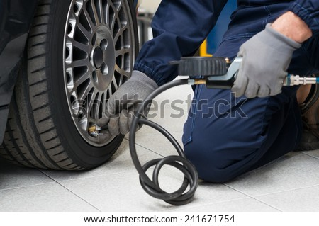 Closeup Of Mechanic At Repair Service Station Checking Tyre Pressure With Gauge - stock photo