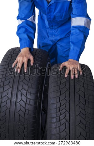 Closeup of mechanic hands with blue uniform holding two tires, isolated on white - stock photo