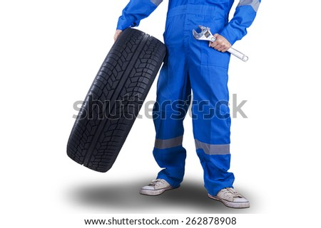 Closeup of mechanic person with a blue uniform holding a wrench and a tire - stock photo