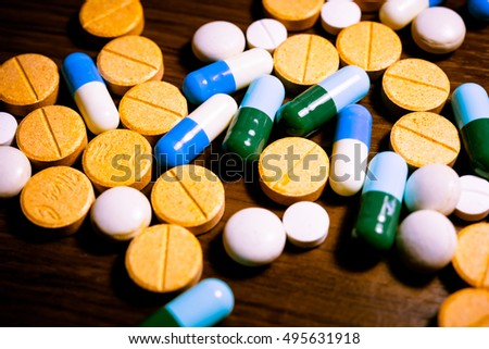 Closeup of medical capsule or pill or drug on wooden background. A lot of colorful medication and pills. - Vintage tone.