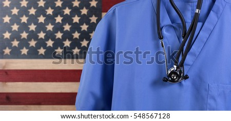 Closeup of medical scrubs with stethoscope against faded boards painted in USA flag background. Healthcare concept for America.