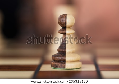 Closeup of merged chess pawns on chessboard - stock photo