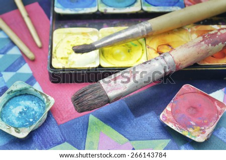 Closeup of messy, used water color paint box and paintbrush - stock photo