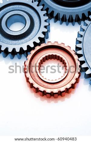 Closeup of metal gears. One red tone, three blue. - stock photo