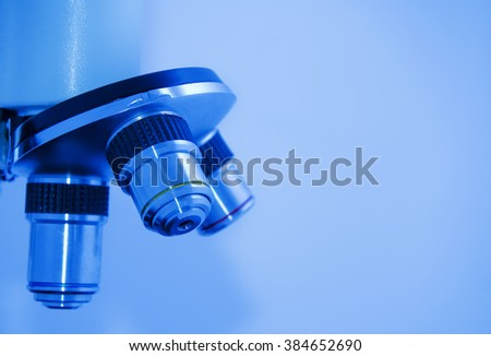Closeup of microscope objectives (in blue tones, with empty space on the right for your text) - stock photo