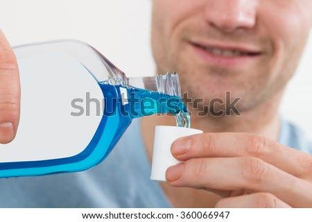 Closeup of mid adult man pouring bottle of mouthwash into cap