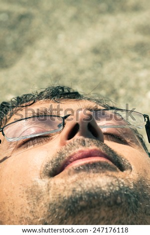Closeup of middle aged man sleeping on the beach. - stock photo