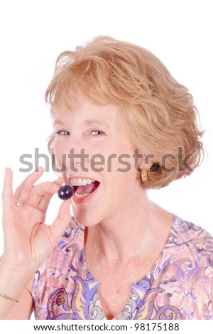closeup of middle-aged woman eating a grape, isolated on white - stock photo