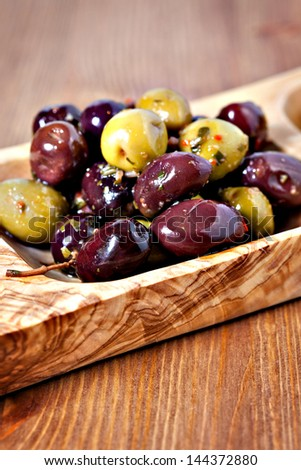 Closeup of mixed marinated olives in olive tree dish on wooden table - stock photo