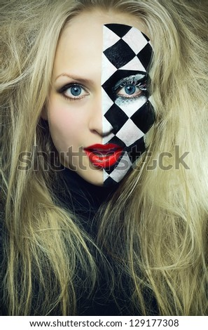Closeup of model with a chess pattern on a half of her face - stock photo