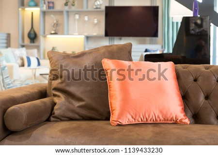 closeup of modern dark brown couch and orange colored pillow flat television and trinkets background - Dark Brown Couch
