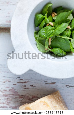 Closeup of mortar with basil leaf and pine seeds, ingredients for the pesto sauce, traditional dressing for Italian pasta. - stock photo