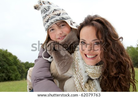 Closeup of mother and daughter in countryside - stock photo