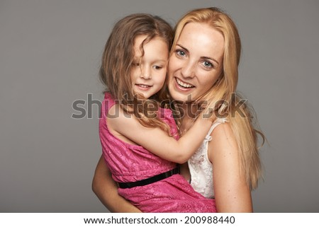 Closeup of mother and her daughter hugging, over gray background - stock photo