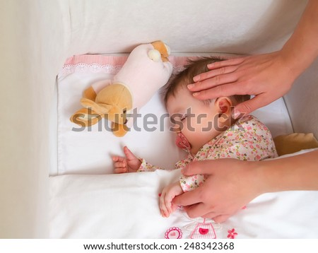 Closeup of mother caressing her cute baby girl sleeping in a cot with pacifier and stuffed toy - stock photo