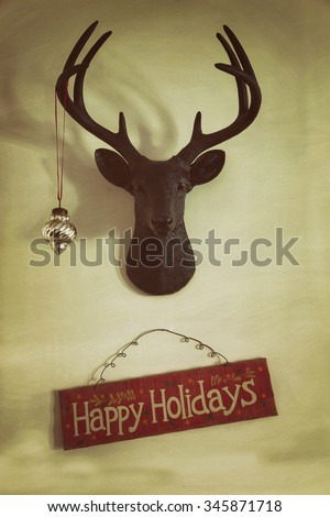 Closeup of mounted deer head with Christmas ornament and holiday sign - stock photo