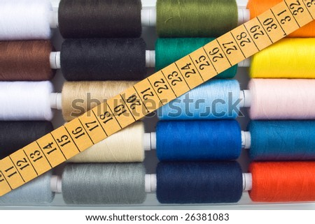 closeup of multicolored sewing spools and meter - stock photo