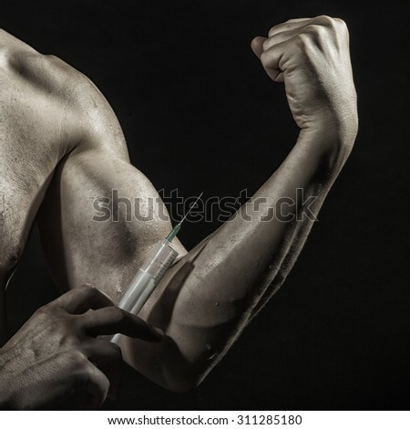 Closeup of muscular male wet arm of young athlete man with big biceps and syringe with thin needl as symbol of medicine anabolocs or drugs making injection on black studio background, square picture - stock photo