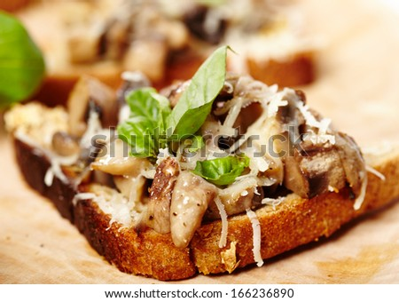 Closeup of mushroom bruschettas decorated with leaves of fresh basil on a wooden board, selective focus - stock photo