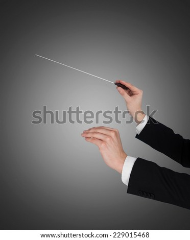 Closeup of music conductor's hands holding baton against gray background