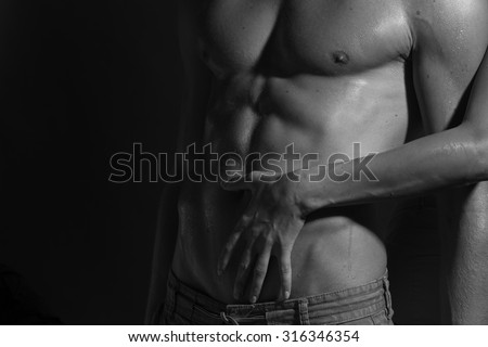 Closeup of naked sexual man with beautiful wet muscular body and female hands touching male six-pack standing in studio black and white, horizontal picture - stock photo