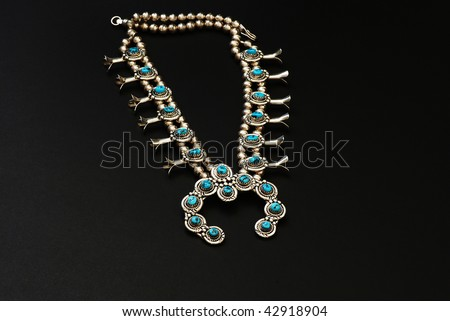 Closeup of  Native American Squash Blossom Necklace isolated on black background.  A beautiful, handcrafted piece of silver and turquoise jewelry. - stock photo