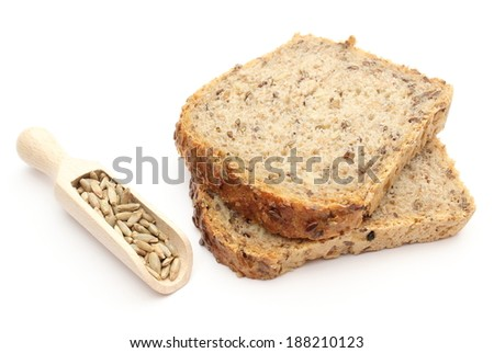 Closeup of natural rye grain on wooden spoons and pieces of bread. Isolated on white background