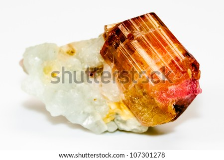 Closeup of natural, uncut and raw Tourmaline gemstone crystal on host rock. - stock photo
