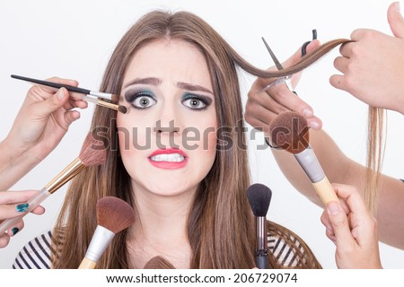 closeup of nervous beautiful blond girl getting hair and makeup done isolated over white - stock photo