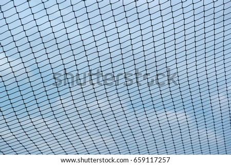 Closeup of net over blue sky and white cloud