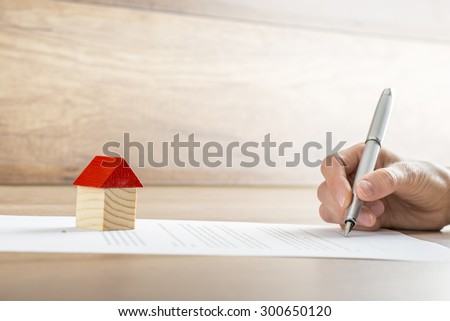 Closeup of new homeowner signing a contract of house sale or mortgage papers with a wooden toy house on the document. Suitable for real estate concept.  - stock photo